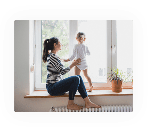 Woman siting on window ledge holding a young girl that is looking out the window.